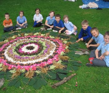 Some children with a flower design they have made in an art workshop
